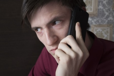 A young man with black smartphone, with an alarming suspicious look