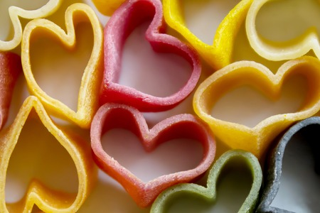 pasta in the form of hearts, different colors, before cooking Banco de Imagens - 119957385