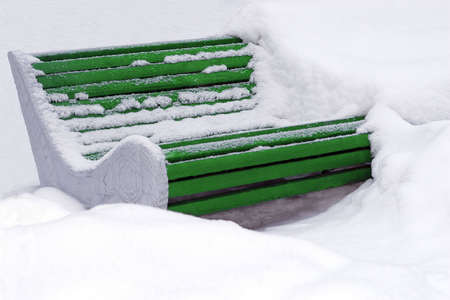 cleaned: Big green wooden bench buried in snow and partly cleaned.
