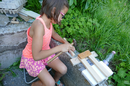 laths: A little girl is making a wood project. Stock Photo