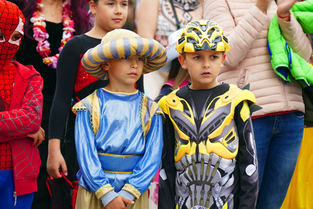 Gabrovo, Bulgaria May 19, 2018. Traditional Carnival of Humor and Satire. Street art. Two boys dressed in different costumes in the audience. Redakční