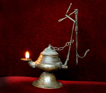 Illuminated antique lamp. Antique bronze thurible with oil. Stock Photo