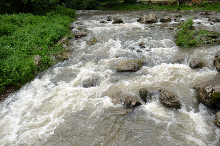 Cloudy turbulent water. Mountain stream after rain.