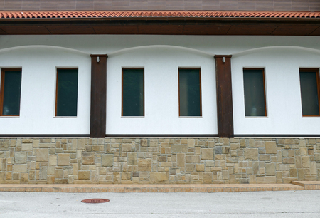 A wall lined with natural stone, a white wall with windows. Symmetrical composition.