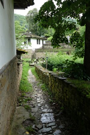 Baojetzi, Bulgaria June 28, 2018. Stone path. Ancient rural architecture from the 18th century. The village is an architectural reserve.