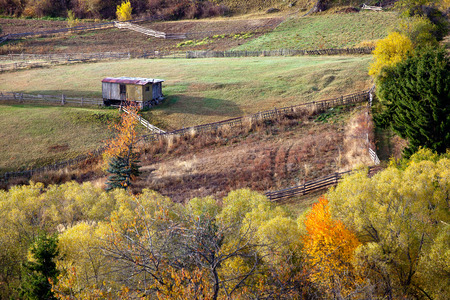 Autumn in the Rhodope Mountains, Bulgaria. In the middle of the woods small fields with fences. Mountain landscape. Stok Fotoğraf