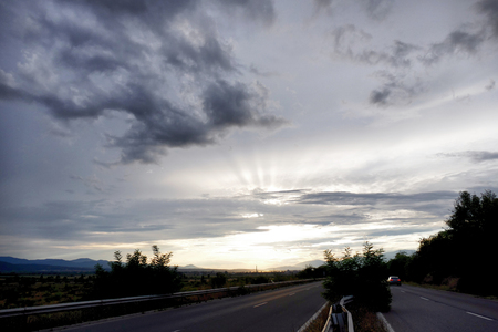 Highway. The sun is hiding behind clouds. Makes sun rays.