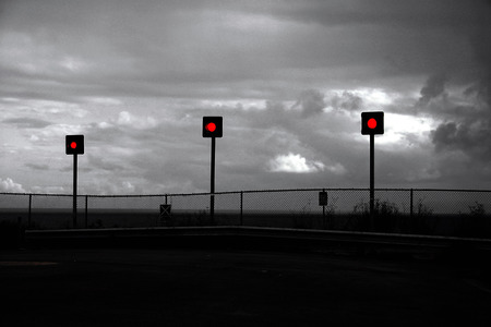 The end of the road. The end of a coastal street. Silent street ending with a fence and a red traffic light. Gray, gloomy mood.