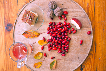 Glass cup of tea with fresh rose hip. Autumn still life with rose hip, walnut, apple and cake.