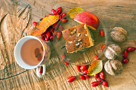 Breakfast, vegan food. Cake with nuts and a cup of tea with fresh rose hips.