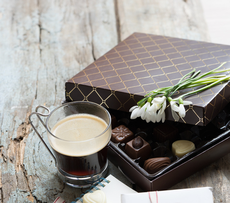Cup of coffee, gift box and chocolate box on a tray