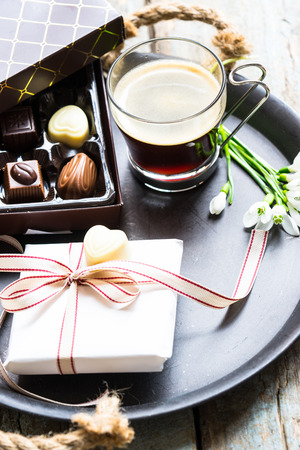 eating chocolate: Cup of coffee, gift box and chocolate box on a tray