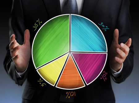progressing: Businessman holding a colorful pie chart Stock Photo