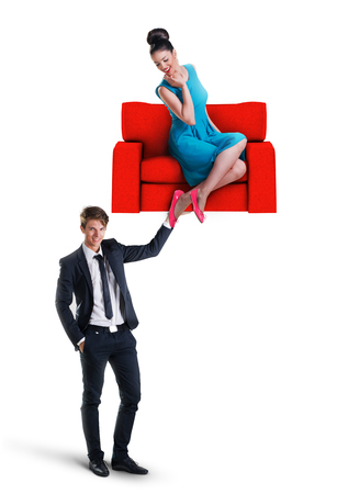 furniture: Man holding a sofa with woman sitting on it Stock Photo
