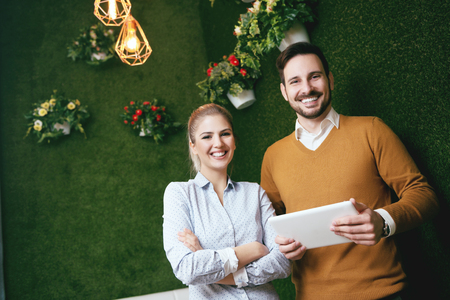 Two young people standing over a green grass wall, holding a tablet Stock Photo