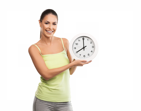Beautiful, young woman holding a clock Stock Photo