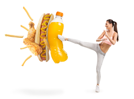 Fit young woman fighting off soda and junk food