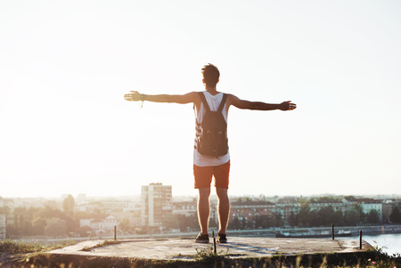 Young man standing on the cliff with a city view, arms wide open Stock Photo