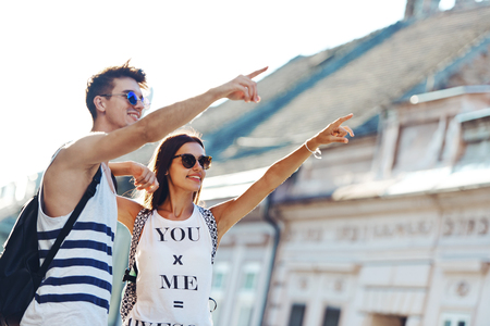 Two young tourists sightseeing a town, pointing with finger