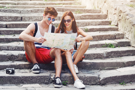 Two young tourists relaxing and examining a guide map in a town
