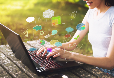 Beautiful young woman sitting in the park, using a laptop, communication concept