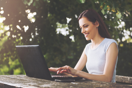 Beautiful young woman sitting in the park, using a laptop