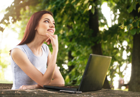 Beautiful young woman sitting in the park, using a laptop, thinking Stock Photo