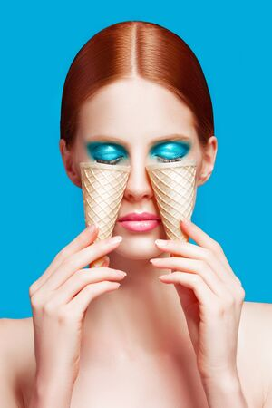 Beautiful woman close up with a ice cream cones, high-quality beauty on blue background