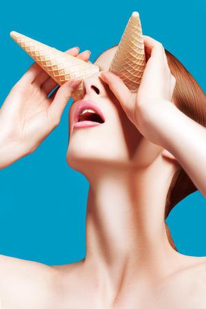 美しい女性が青の背景に高品質の美容のアイス クリーム コーンでクローズ アップ