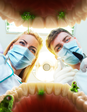 Two dentists examining teeth, view from the inside of the mouth