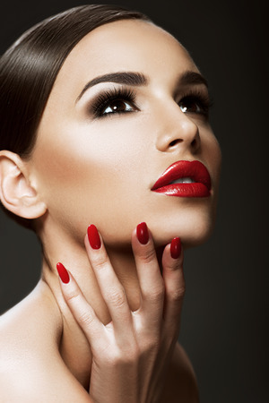 Beautiful woman portrait, beauty on dark background, red nails