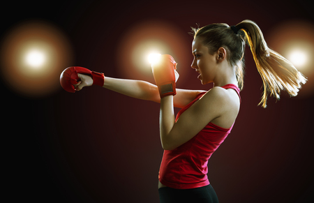 Fit, young woman boxer punching, dark background