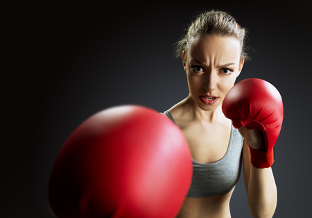 Fit, young woman boxer, black background Stock Photo