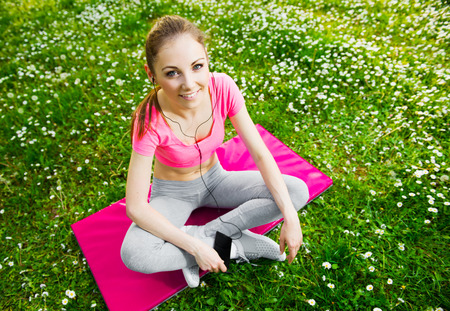 Fit young woman using a cell phone outdoors, healthy lifestyle