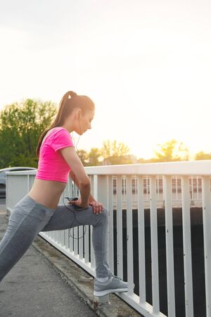 Fit young woman stretching outdoors,on the bridge, healthy lifestyle