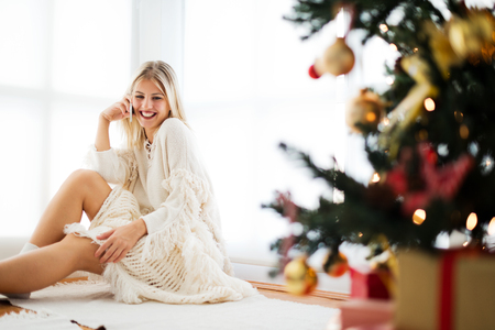Young woman sitting next to a Christmas tree, talking over the phone