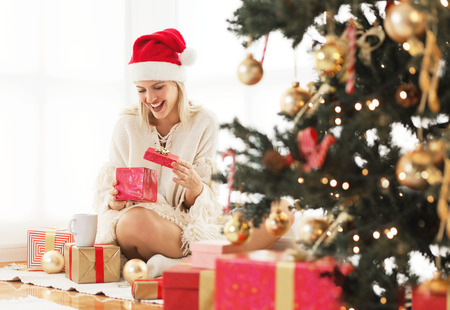 Young woman opening a present on Christmas morning