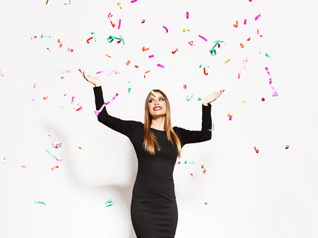 Young woman celebrating, confetti falling