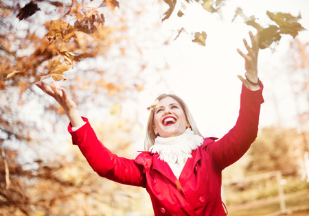 Happy, young woman throwing autumn leaves Standard-Bild