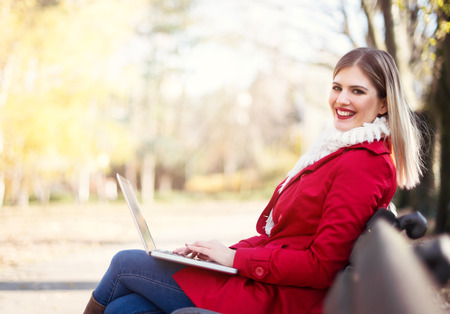 Young woman sitting on the bench, using a laptop