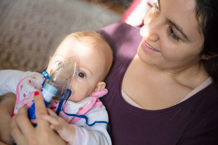 Little baby girl in arms of her mother, usign inhalator as a non invasive respiratory therapy.