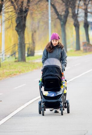 Young woman walking with her baby in strollers in autumn, on a windy day. Stock Photo