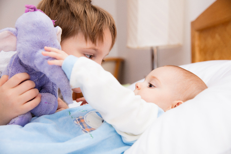 six month old: Six year old toddler sharing tender and affectionate moments with his six month old baby sister. Stock Photo