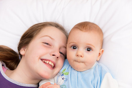 amusment: Nine year old girl amusing her little baby sister, sharing some tender and affectionate moments together, smiling, having fun. Stock Photo