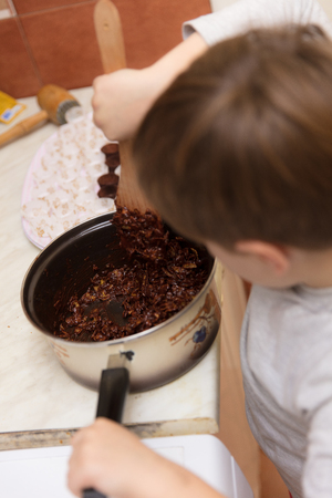 them: Little boy making corn flake chocolate cookies at home, for holidays, eating some of them during the process.