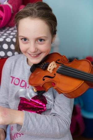 Little girl playing violing, practising at home.