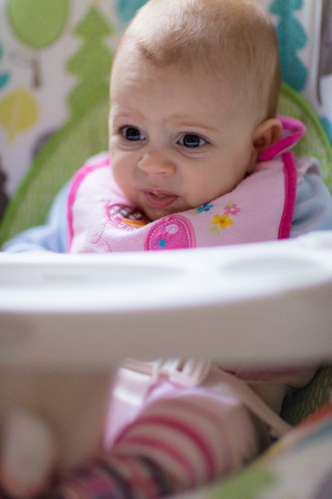 baby facial expressions: Little baby girl making different facial expression while having a first meal in an arm chair and playing. Stock Photo