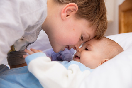 Six year old toddler sharing tender and affectionate moments with his six month old baby sister. Stock Photo