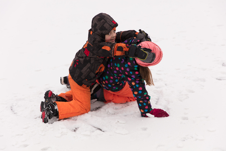 Little boy and girl, brother and sister, havins some fun in winter on a frozen lake, playing on ice. Reklamní fotografie