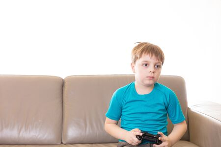 Little boy playing some video games at home using a controller, making different expressions. Stock Photo